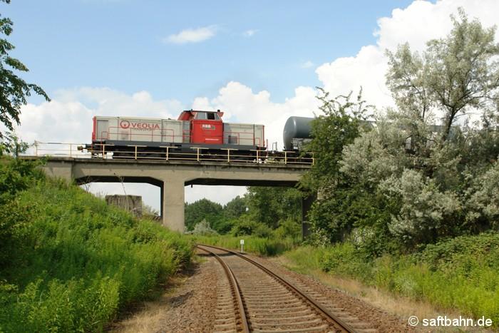 In Bitterfeld Nord überquert  die Schiene der dortigen Chemie- und Werksbahn das Saftbahngleis. Am 02.07.2009 ist V133 der Regiobahn Bitterfeld-Berlin GmbH mit einigen Kesselwagen unterwegs und gelangt durch die Eisenbahnüberführung schnell zu den einzelnen Chemie-Arealen. Bis zur Wende 1989 konnte man noch mit einer Verbindungskurve von Stumsdorf kommend auf die Infrastruktur der Werksbahn fahren.